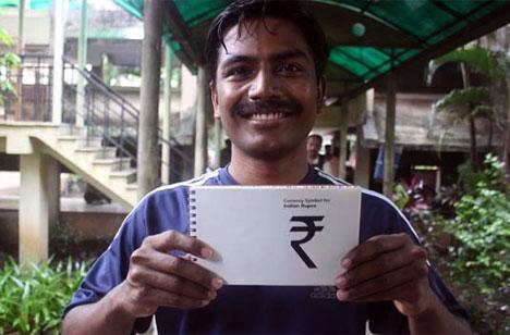 Udaya Kumar muestra el símbolo de la rupia, diseñado por él. Foto: Daiji World.