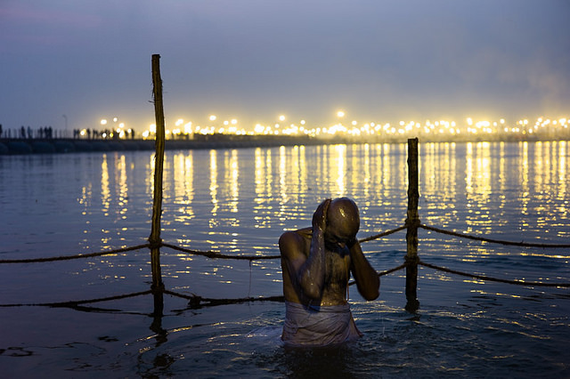 Indian man bathing in the Ganges river in Haridwar