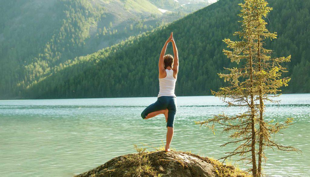 Mujer practicando yoga junto al río Ganges en Rishikesh