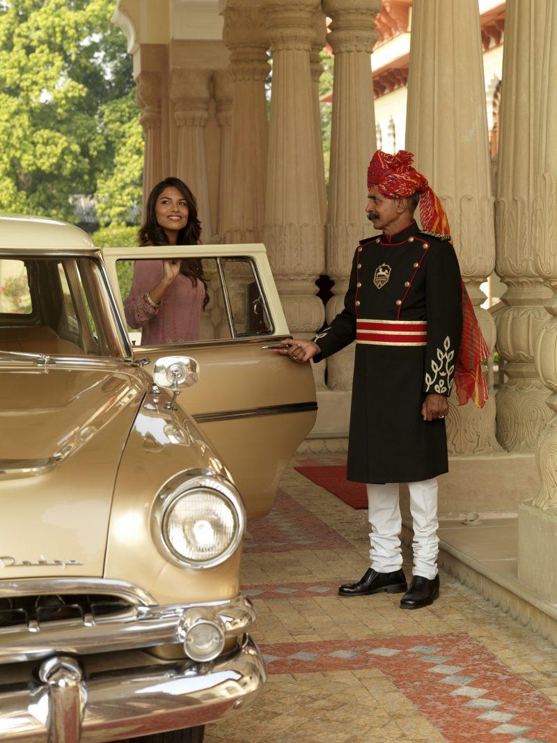 India con chófer. Mujer saliendo de coche clásico en hotel Taj Rambagh Palace.