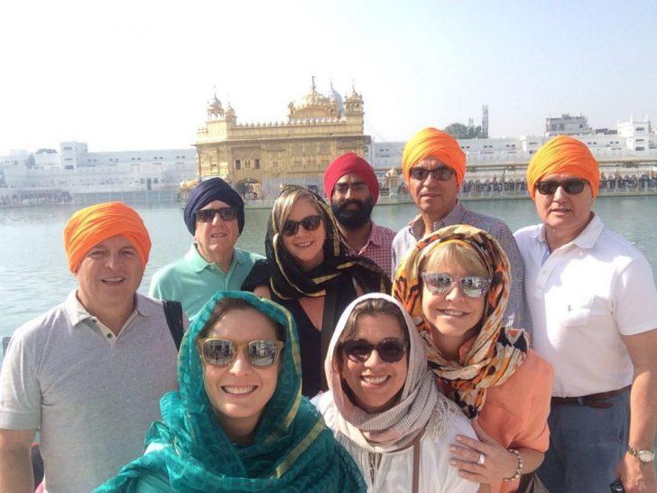 Grupo de viajeros frente al templo dorado con su guía acompañante