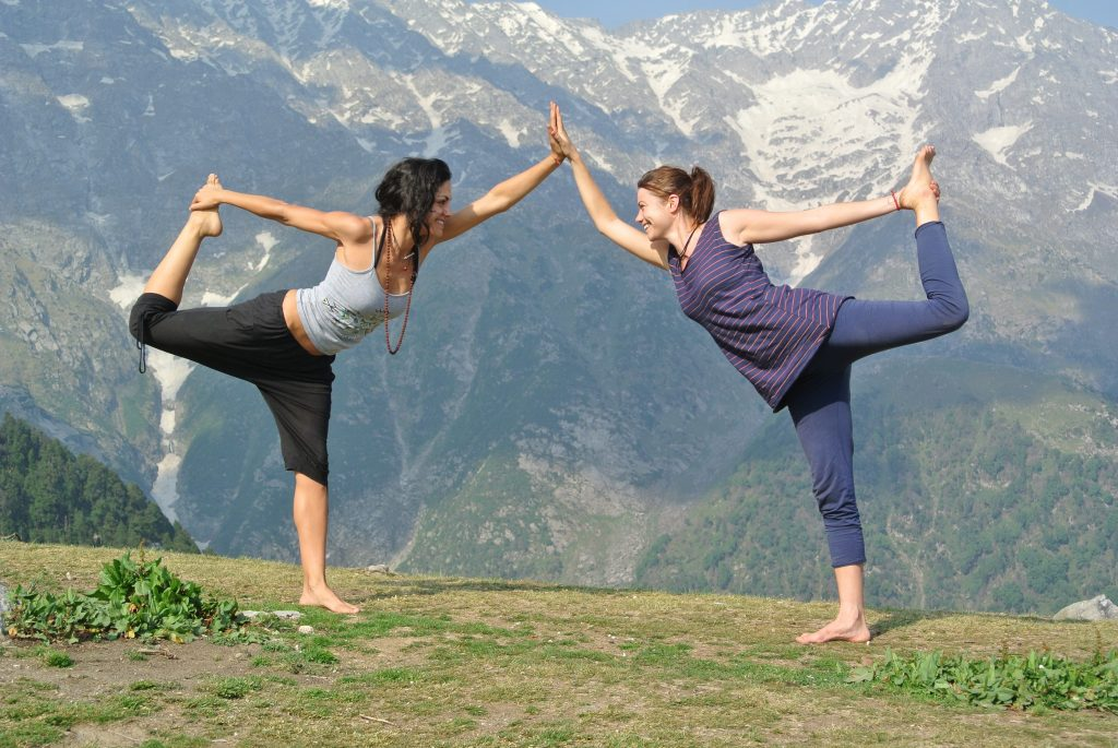 Two girls practice yoga in front of the mountains of Dharamsala