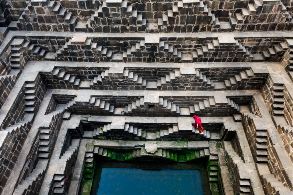 Stairs and woman descending to the stepped well Chand Baori
