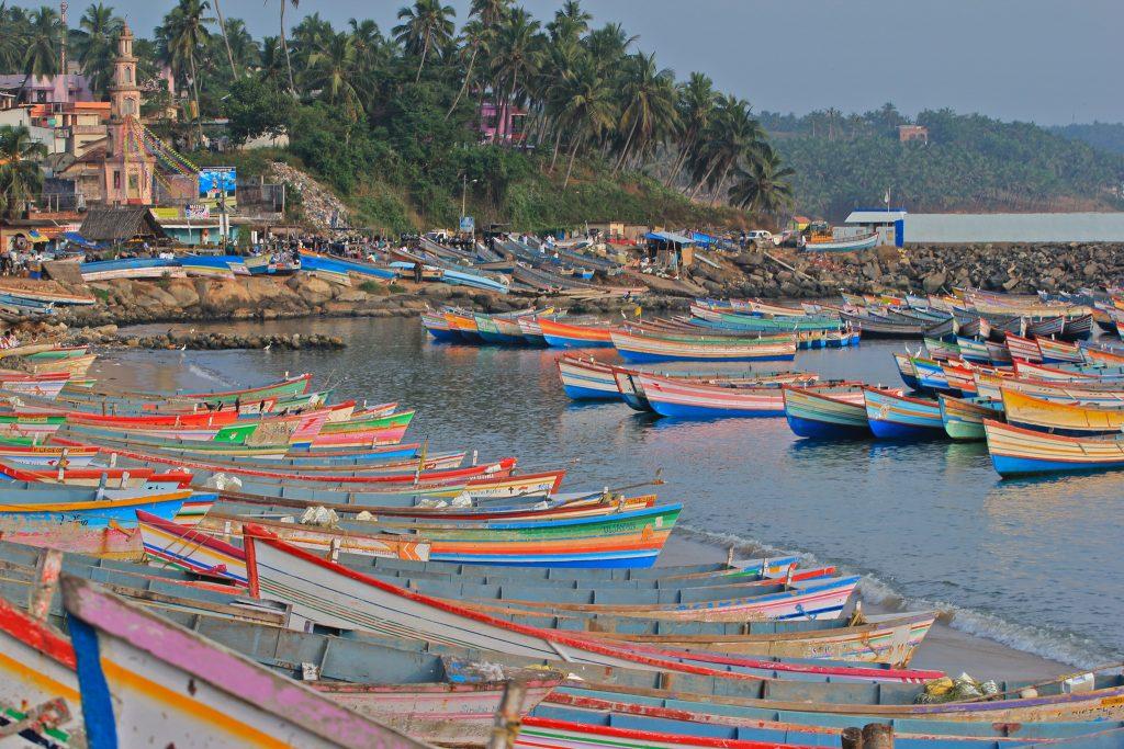Mezquita y barcas de pescadores de colores en puerto de Vizhinjam