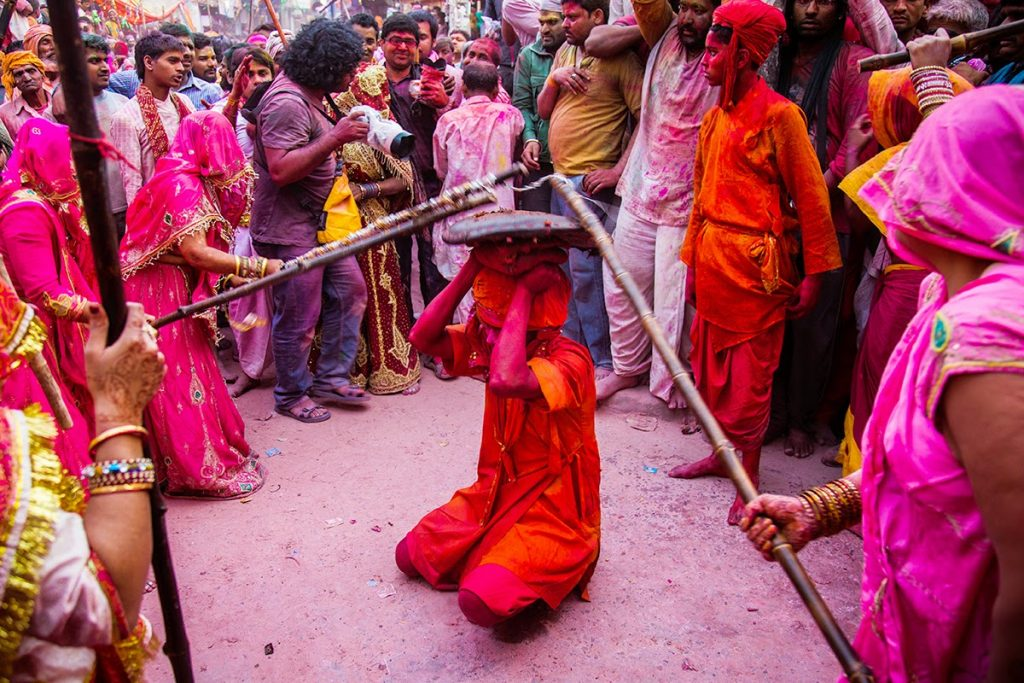 Women hitting a stick on a man in Holi in Brindavan.