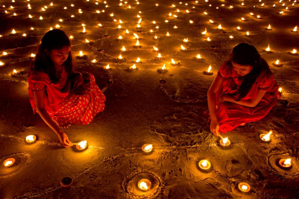 Velas y rangolis encendiéndose e n Diwali