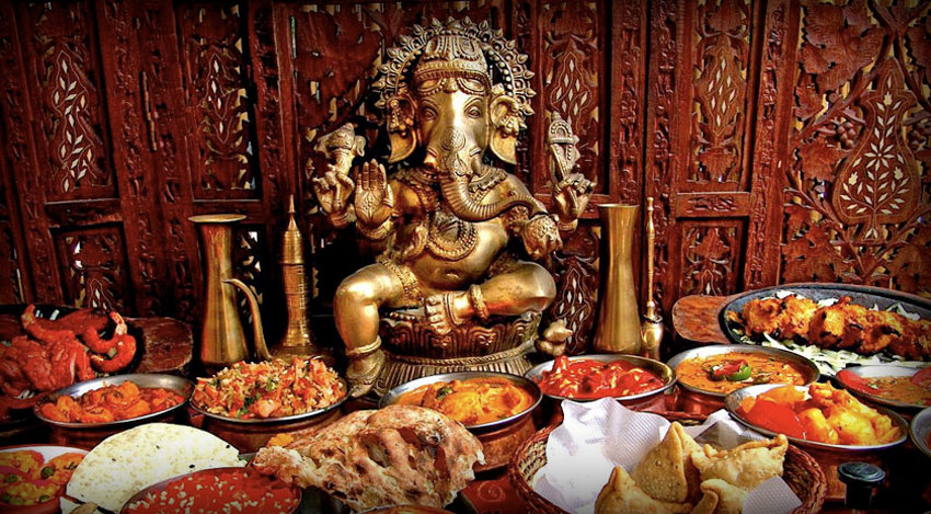 Different dishes of Indian food next to statue of Ganesha