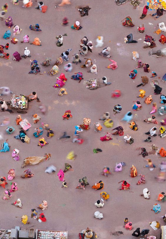 People with saris and colored clothes bathing in the river Ganges
