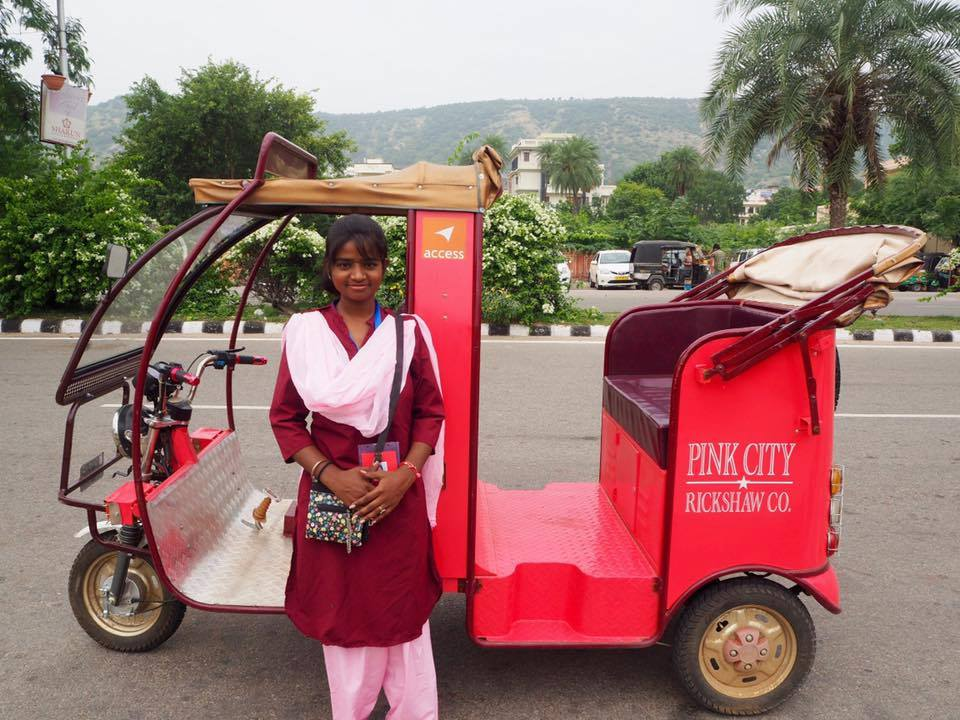 Young driver next to pink tuk tuk of Pink City Rickshaw