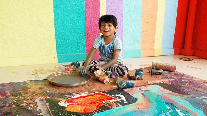 Niño junto a paredes de colores y rangoli en India