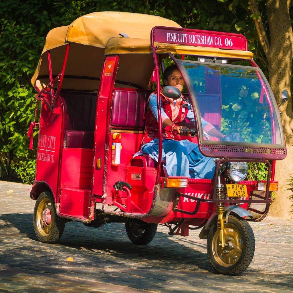 Mujer conduciendo un rickshaw rosa en Jaipur
