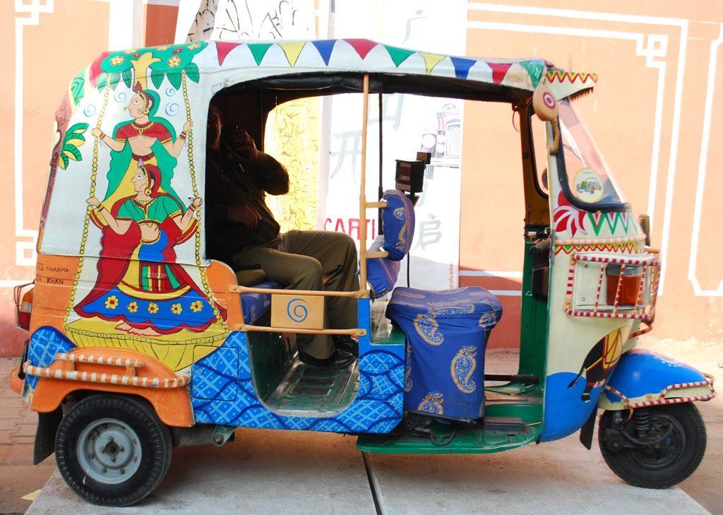 Rickshaw de colores y mujeres indias en Jaipur
