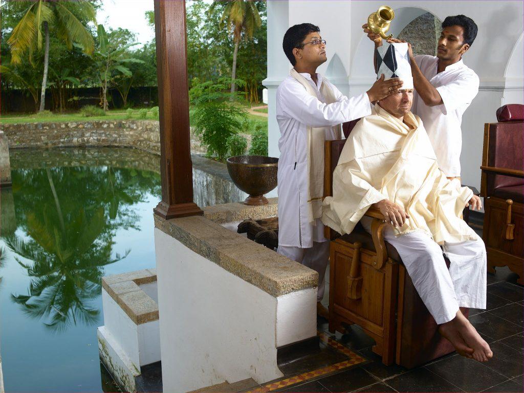 Hombre y profesionales de ayurveda en resort CGH Earth Kerala