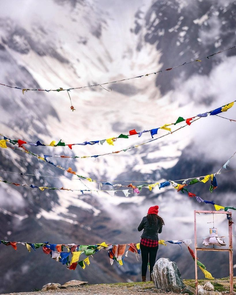 Kunzum Pass, prayer flags and adventurer in Spiti Valley